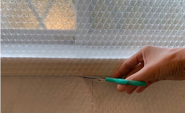窓枠に貼ったプチプチをハサミでカット